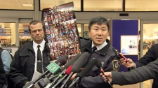 Vancouver Police Chief Jim Chu displays a poster featuring photos of 104 suspects in the June 16 Stanley Cup riot. Nov. 16, 2011. (CTV)