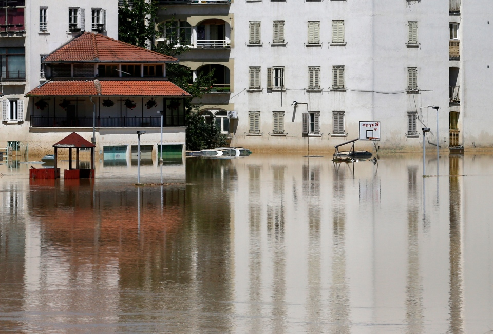 Buildings are reflected in a flooded street in Obrenovac, Serbia, Monday, May 19, 2014. (AP / Darko Vojinovic)