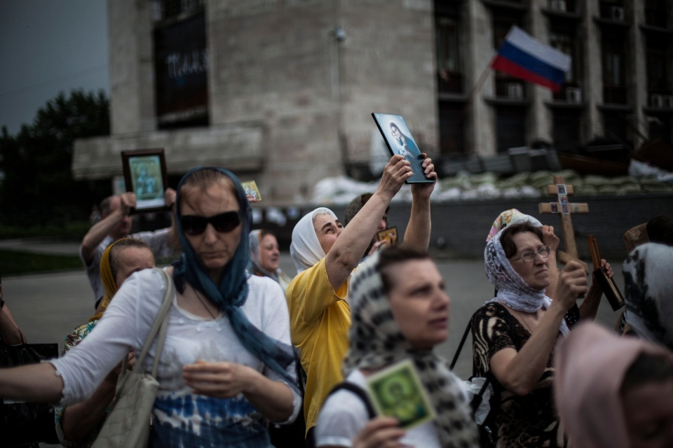 A pro-Russian woman holds up an Orthodox symbol while attending a public prayer meeting for peace in front of the occupied administration building in Donetsk, eastern Ukraine, Monday, May 19, 2014. (AP / Manu Brabo)