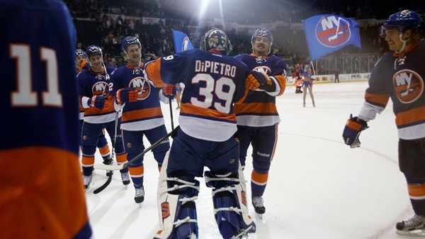 New York Islanders goalie Rick DiPietro celebrates with teammates after defeating the Montreal Canadiens 4-3.  Nov. 17, 2011. (AP Photo/Kathy Willens)