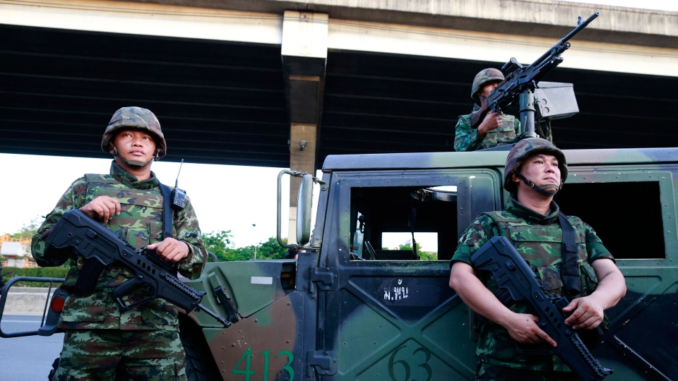 Thai soldiers take up position on a street outside the Centre for the Administration of Peace and Order (CAPO) after soldiers were sent in to seize the center in Bangkok, Thailand on Tuesday, May 20, 2014. (AP / Wason Wanichakorn)