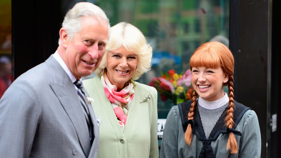 Prince Charles and his wife Camilla share a laugh with actress Katie Kerr portraying Anne of Green Gables in Charlottetown, P.E.I. on Tuesday, May 20, 2014. (Paul Chiasson / THE CANADIAN PRESS)