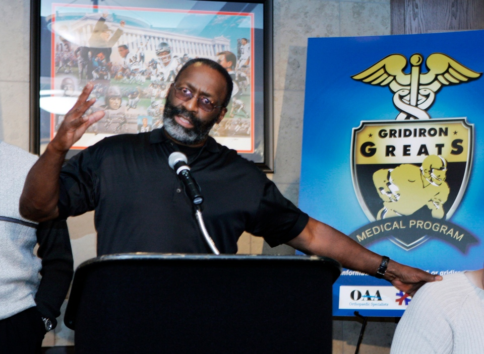 Former NFL player J.D. Hill gestures during a news conference in Chicago, where an initiative was announced that would help retired NFL players in dire need of medical care to receive care with millions of dollars in donated medical services through the Gridiron Greats Assistance Fund, May 13, 2008. (AP / Charles Rex Arbogast)