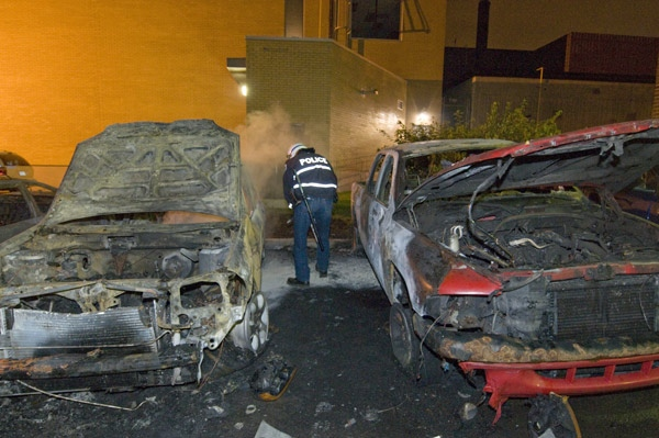 Montreal police extinguish a fire burning in a firefighters car in front of a fire-station in Montreal on Sunday, August 10, 2008. (Peter McCabe / THE CANADIAN PRESS)