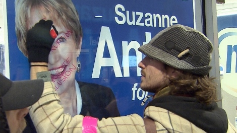 An Occupy Vancouver protester writes on a Suzanne Anton campaign poster. Nov. 18, 2011. (CTV)
