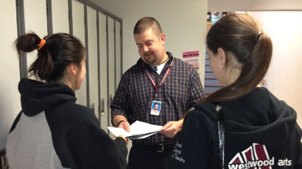 Dave Shoesmith hands out permission slips at Westwood Collegiate in Winnipeg, Man.