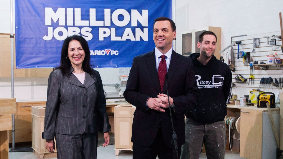 Ontario PC Leader Tim Hudak, centre, flanked by PC candidate for Mississauga South Effie Triantafilopoulos, left, and small business owner Shane Ritcey, right, speaks in Mississauga on Monday, May 19, 2014. (Michelle Siu / THE CANADIAN PRESS)