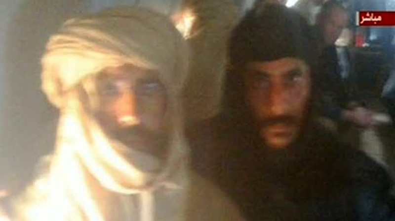 In this image from Libyan Television, Seif al-Islam Gadhafi, left, is guarded by a Libyan fighter as he is transported to Zintan, Libya, by a transport aircraft following his capture near the Niger border early Saturday Nov 19 2011. (AP Photo/ Libyan Television via APTN)