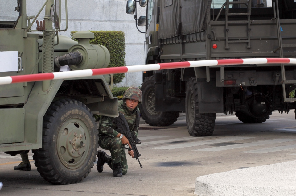 An armed Thai soldier takes position behind a military vehicle in the compound of the Army Club shortly after the military staged a coup Thursday, May 22, 2014 in Bangkok, Thailand. (AP / Apichart Weerawong)