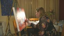Parkinson's patient Beverly Lavender is seen painting a portrait.