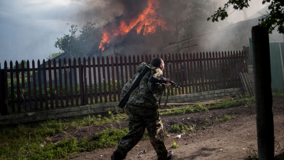 A pro-Russian armed man runs past a burning house after it was set on fire by a mortar shell, on the outskirts of the town of Lysychansk, Ukraine, on Thursday, May 22, 2014. (AP / Evgeniy Maloletka)