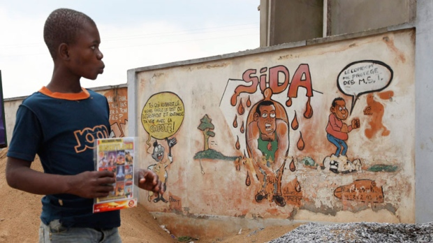 A child walks past graffiti warning citizens to protect themselves from HIV and AIDS in Yaounde, Cameroon, Tuesday, Oct. 11. 2011. (AP / Sunday Alamba)