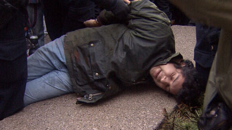 An Occupy Vancouver protester is detained near the intersection of Robson and Howe streets. Nov. 21, 2011. (CTV)