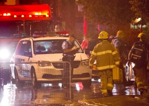 Police and fireman work at the rear of an auditorium where a gunman shot and killed at least one person during the PQ victory rally on September 5, 2012, in Montreal. (Paul Chiasson / THE CANADIAN PRESS)
