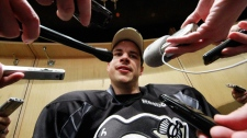 Pittsburgh Penguins' Sidney Crosby is surrounded by reporters at his locker after participating in a game day morning skate in preparation for his return to NHL hockey action against the New York Islanders, in Pittsburgh, Monday, Nov. 21, 2011. (AP /  Gene J. Puskar