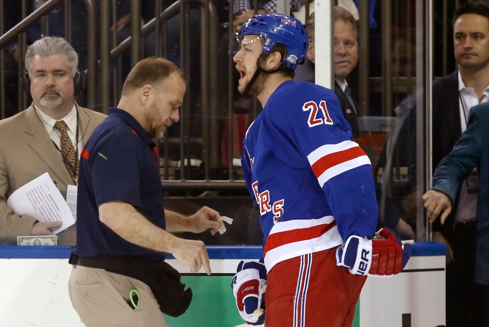 In this May 22, 2014 photo, New York Rangers center Derek Stepan (21) leaves the ice with a member of the Rangers staff after taking a hit from Montreal Canadiens forward Brandon Prust during the first period of Game 3 of the NHL hockey Stanley Cup playoffs Eastern Conference finals in New York. (AP Photo/Kathy Willens)