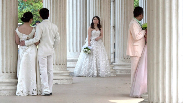 bride waits for her groom as other couples pose for wedding photos ...