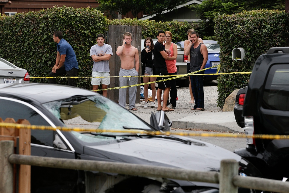 People look at a black BMW sedan driven by a drive-by shooter in Isla Vista, Calif on Saturday, May 24, 2014. (AP / Jae C. Hong)