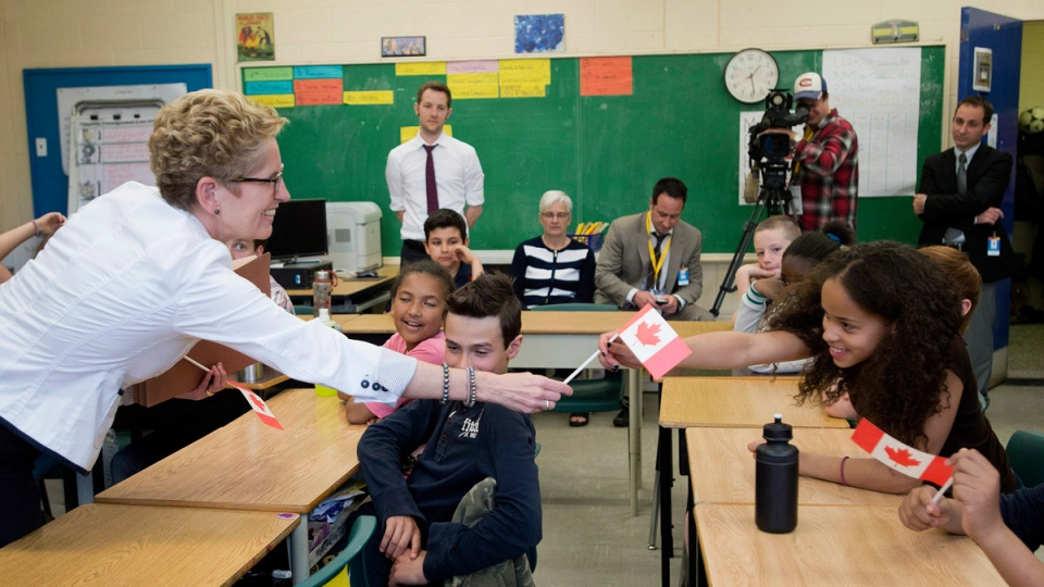 Ontario Liberal Leader Kathleen Wynne, left, hands out Canadian flags to students at Ecole Elementaire Pierre-Elliot-Trudeau school during a campaign stop in Toronto on Friday, May 23, 2014. (THE CANADIAN PRESS/Nathan Denette)