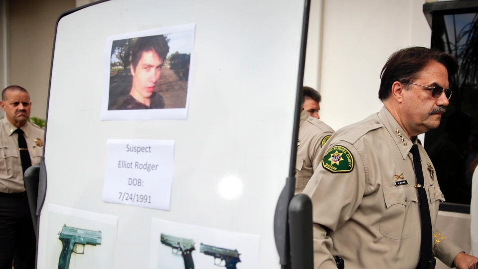 Santa Barbara County Sheriff Bill Brown, right, walks past a board showing the photos of suspected gunman Elliot Rodger and the weapons he used in Friday night's mass shooting that took place in Isla Vista, Calif., after a news conference in Santa Barbara, Calif., Saturday, May 24, 2014. (AP / Jae C. Hong)