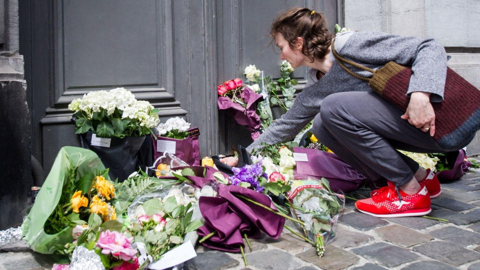A woman lays flowers at the Jewish Museum in Brussels, Sunday May 25, 2014. (AP / Geert Vanden Wijngaert)