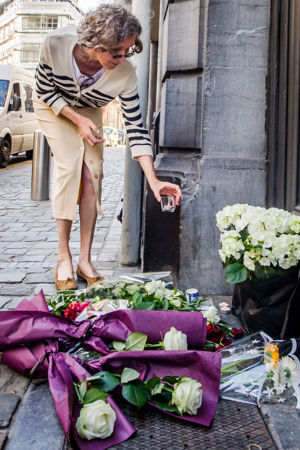 A woman places a candle next to flowers at the Jewish Museum in Brussels, Sunday May 25, 2014. (AP / Geert Vanden Wijngaert)