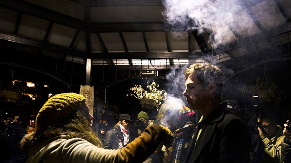 An Occupy Toronto protester burns wet sage smoke around shortly before the 12:01 a.m. deadline of City of Toronto bylaw officers' eviction notices on tents and structures in St. James Park in Toronto on Tuesday, Nov. 22, 2011. (Nathan Denette / THE CANADIAN PRESS)