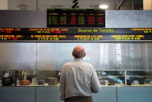A man watches the financial numbers on the digital ticker tape at the TMX Group in Toronto, Ont.'s financial district on Friday, May 9, 2014. (Darren Calabrese / THE CANADIAN PRESS)