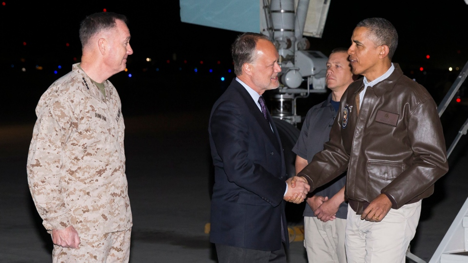 President Barack Obama, right, is greeted by US Ambassador to Afghanistan James Cunningham, center, and Marine General Joseph Dunford, commander of the US-led International Security Assistance Force (ISAF), as he steps off Air Force One after arriving at Bagram Air Field for an unannounced visit, north of Kabul, Afghanistan, Sunday, May 25, 2014. (AP / Evan Vucci)