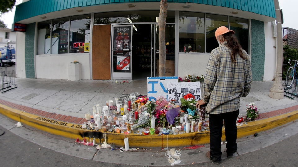 A passerby pays his respects at a makeshift memorial in front of the IV Deli Mart in the Isla Vista area near Goleta, Calif. on Sunday, May 25, 2014. (AP / Chris Carlson)