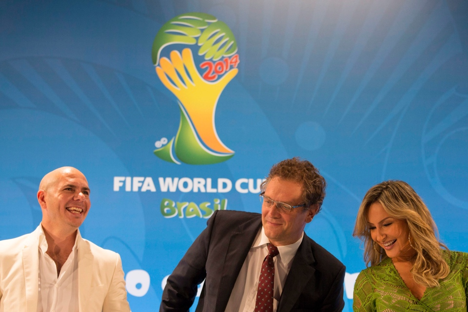 Brazilian singer Claudia Leitte, right, FIFA Secretary General Jerome Valcke, center, and rapper Pitbull react during a news conference at the Maracana stadium in Rio de Janeiro, Brazil, Thursday, Jan. 23, 2014. Claudia Leitte and Pitbull will perform with Jennifer Lopez the official song for the 2014 World Cup. (AP Photo/Felipe Dana)