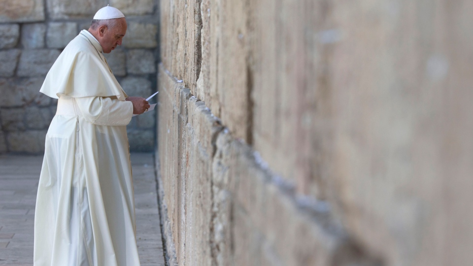 Pope Francis places a note in an envelope before placing it in on of the cracks between the stones of the Western Wall, the holiest place where Jews can pray, in the old city of Jerusalem, Israel, Monday, May 26, 2014. (AP / Andrew Medichini)