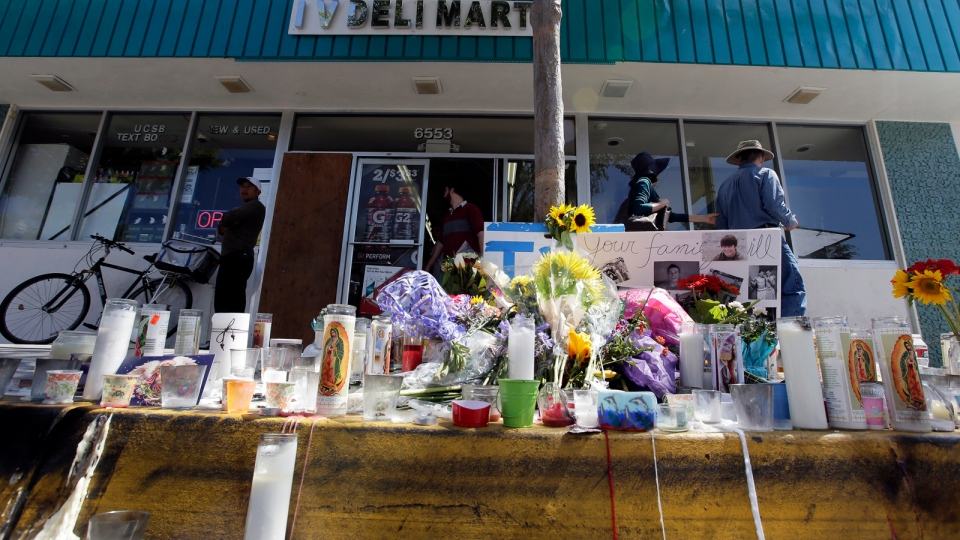 People walk by a makeshift memorial in front of the IV Deli Mart, where part of Friday night's mass shooting took place by a drive-by shooter Sunday, May 25, 2014, in the Isla Vista area near Goleta, Calif. (AP / Chris Carlson)