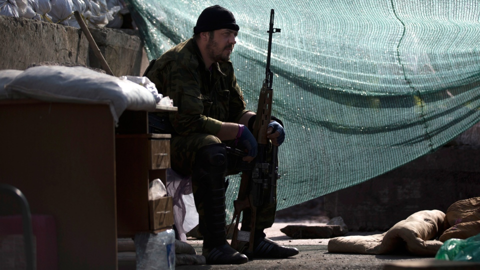 A pro-Russian armed militant guards a checkpoint blocking a major highway which links Kharkiv, outside Slovyansk, Ukraine, Monday, May 26, 2014. (AP / Alexander Zemlianichenko)