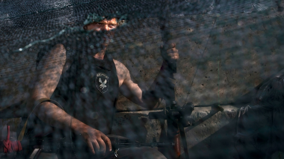 A pro-Russian armed militant wearing a shirt bearing an emblem of a former Ukrainian special force's police unit 'Berkut,' which means golden eagle, is seen through a camouflage net as he guards a checkpoint blocking the major highway which links the Russian city of Rostov-on-Don, and Kharkiv, outside Slovyansk, Ukraine, Monday, May 26, 2014. (AP / Alexander Zemlianichenko)
