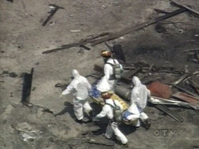 Officials remove a body found among the wreckage at the site of the propane blast on Tuesday, Aug. 12, 2008.