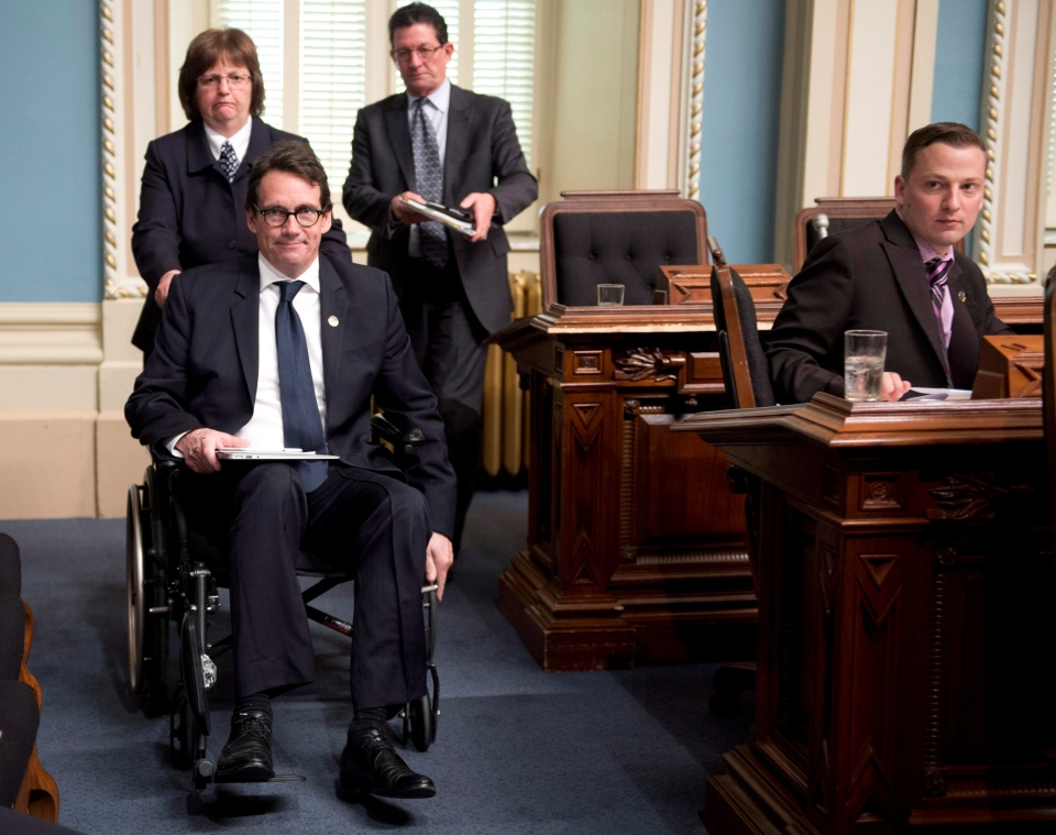 Quebec Opposition MNA Pierre Karl Peladeau leaves question period in a wheelchair on Monday, May 26, 2014 at the legislature in Quebec City. (Jacques Boissinot / THE CANADIAN PRESS)