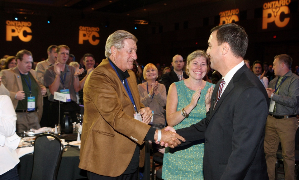 Party leader Tim Hudak, shakes hands with former Premier Mike Harris, next to his wife Deb Hutton at the Ontario Progressive Conservative party Policy Convention in London, Ont., Saturday, Sept. 21, 2013. (Dave Chidley / THE CANADIAN PRESS)