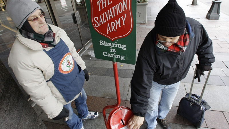 In this Dec. 17, 2008 file photo, Donald Baca, right, drops money into a Salvation Army red kettle as bell ringer Mark Pearson looks on in downtown Seattle. (AP Photo)