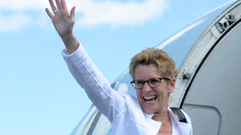 Ontario Liberal Leader Kathleen Wynne waves as she boards her aircraft leaving Thunder Bay, Ont., on Monday May 26, 2014. (Frank Gunn / THE CANADIAN PRESS)