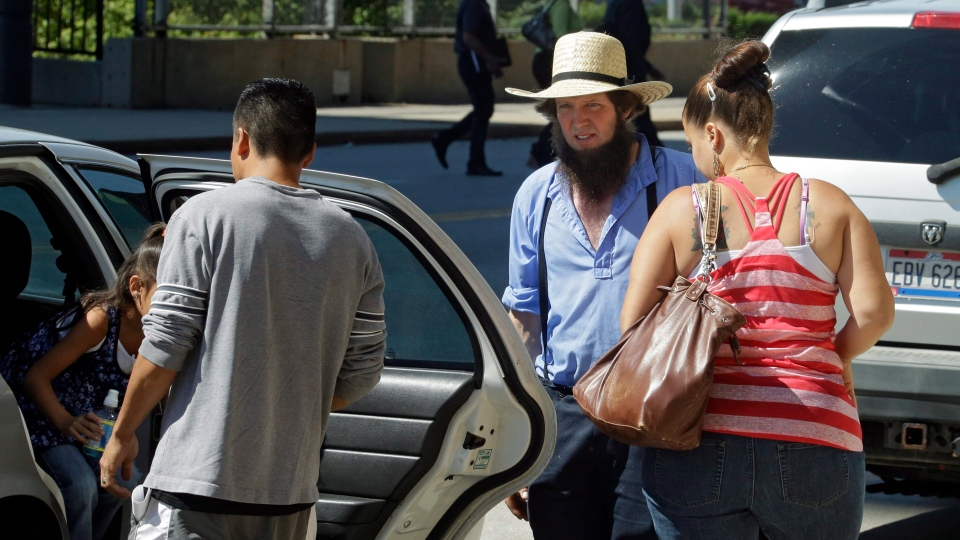 An Amish man waits for others to emerge from a taxi before entering the U.S. courthouse in Cleveland Wednesday, Sept. 12, 2012. (AP Photo/Mark Duncan)