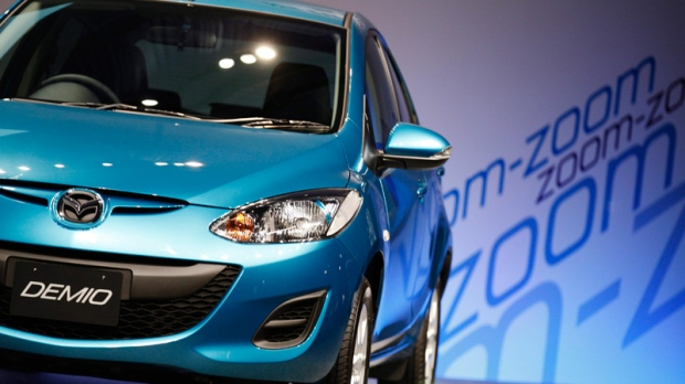 A new Mazda Demio is displayed during a press conference in Tokyo Thursday, June 30, 2011. Mazda Motor Corp. began selling the Demio, known as Mazda2 overseas, in Japan on Thursday, offering a version packed with its efficient gas engine called 'Skyactiv' technology. (AP / Hiro Komae)