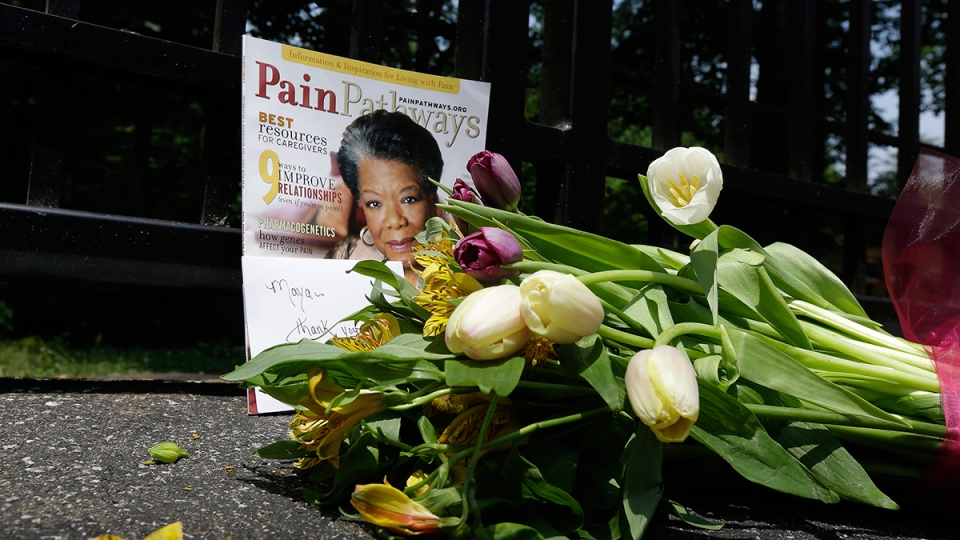 A bouquet of flowers and a magazine showing Maya Angelou on the cover lie outside a gate at the home of Angelou in Winston-Salem, N.C., Wednesday, May 28, 2014. (AP / Gerry Broome)