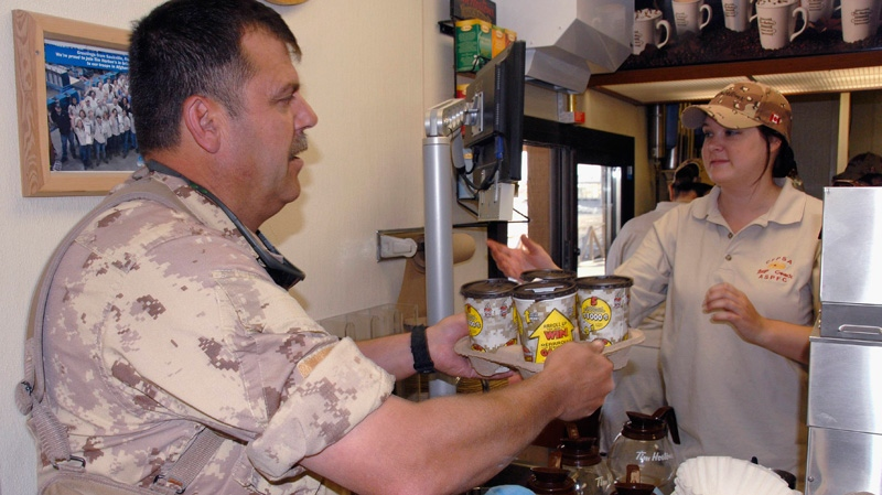 A solider based out of CFB Petawawa, Ont., buys Tim Hortons coffee in Kandahar, Afghanistan, on Saturday, April 21, 2007 (Combat Camera/Sgt Roxanne Clowe)