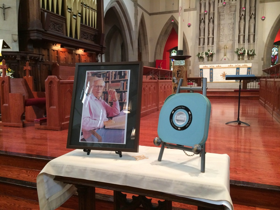 A 3/4 inch videocassette case containing the ashes of former CBC anchor Knowlton Nash sits beside his portrait at his funeral in Toronto on Wednesday, May 28, 2014. (THE CANADIAN PRESS/CBC - Ioanna Roumeliotis)