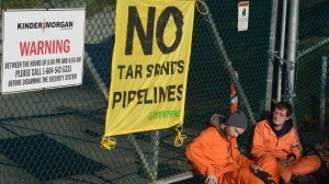 Greenpeace activists sit on the ground as they chain themselves to the gate at the Kinder Morgan facility in Burrard Inlet in Burnaby, B.C. Wednesday, Oct. 16, 2013. (THE CANADIAN PRESS/Jonathan Hayward