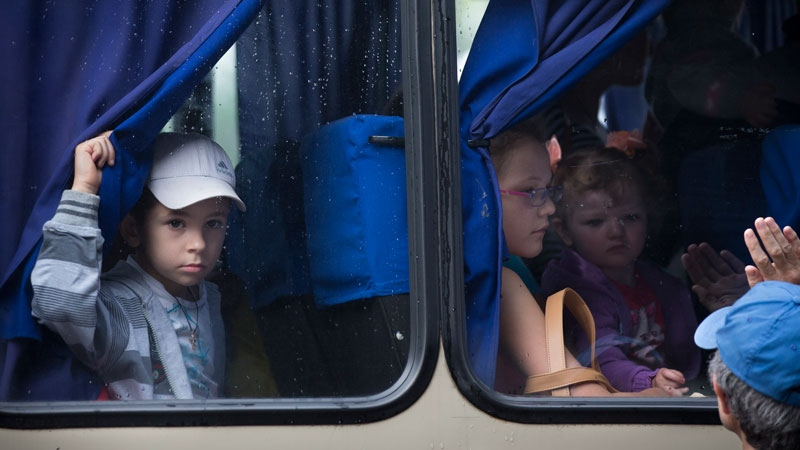 Children look through bus windows while leaving the city fearing shelling attacks during a fighting between Ukrainian government forces and pro-Russian militants in Slovyansk, Ukraine, Thursday, May 29, 2014.  (AP Photo/Alexander Zemlianichenko)