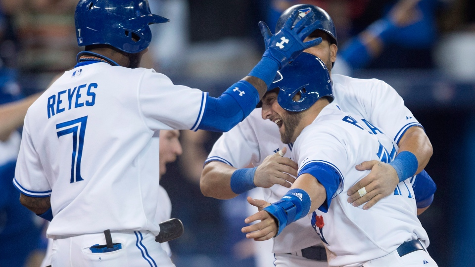 Toronto Blue Jays' Kevin Pillar, right, celebrates scoring the winning run with teammates Jose Reyes, left, and Melky Cabrera in the 9th against the Tampa Bay Rays in Toronto on Wednesday, May 28, 2014. (Darren Calabrese / THE CANADIAN PRESS)