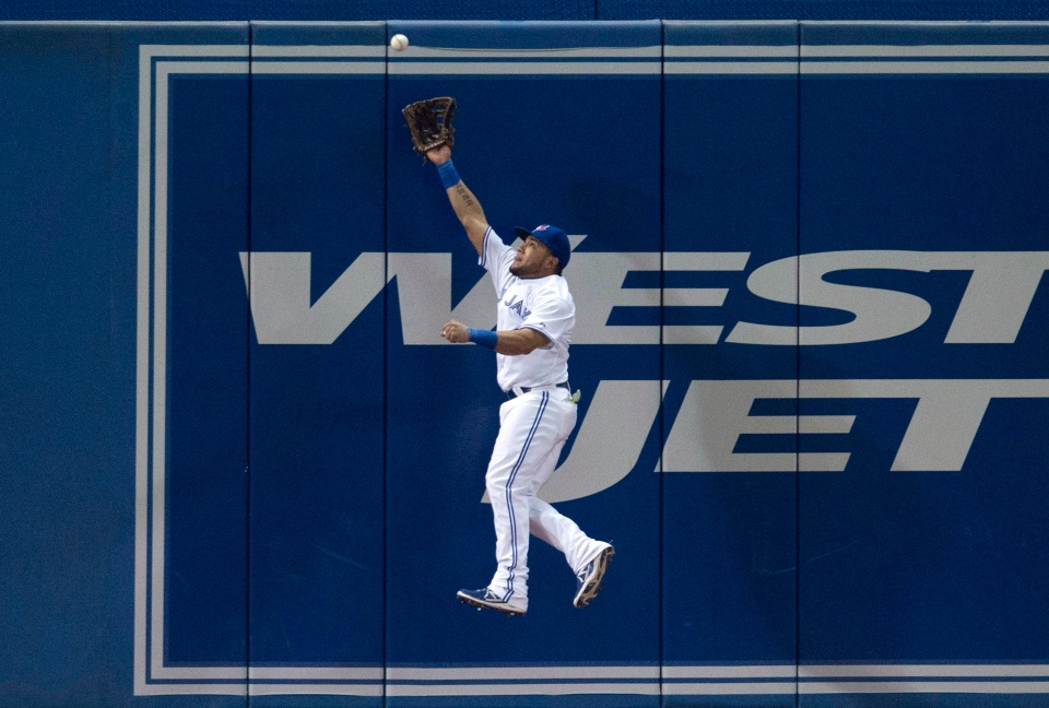 Toronto Blue Jays' Melky Cabrera makes a leaping catch at the wall to rob Tampa Bay Rays' Evan Longoria of a hit during sixth inning MLB baseball action in Toronto on Wednesday, May 28, 2014. (Darren Calabrese / THE CANADIAN PRESS)