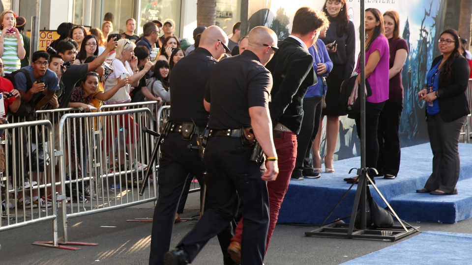 A fan is walked off carpet in handcuffs after allegedly attacking Brad Pitt at the world premiere of 'Maleficent' at the El Capitan Theatre on Wednesday, May 28, 2014, in Los Angeles. (AP Photo / Matt Sayles)